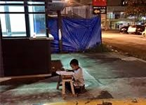 homeless-boy-who-uses-light-from-fast-food-restaurant-to-do-his-school-work